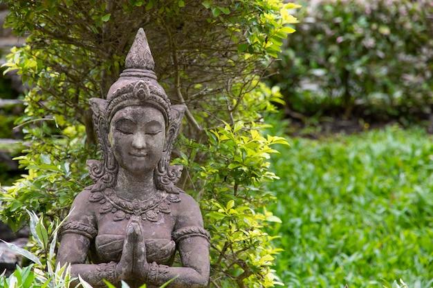 Estátua de pedra velha de uma mulher para a decoração do jardim.