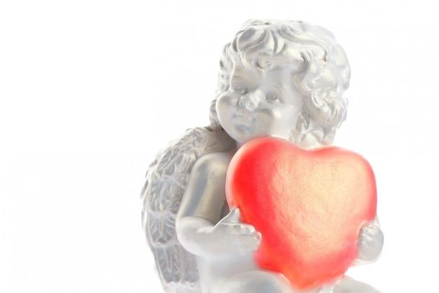 Estátua de querubim isolada na superfície branca, anjo mantém o coração, amor