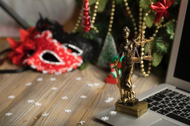 Estátua de themis colocada em um laptop. plano de fundo do dia de ano novo