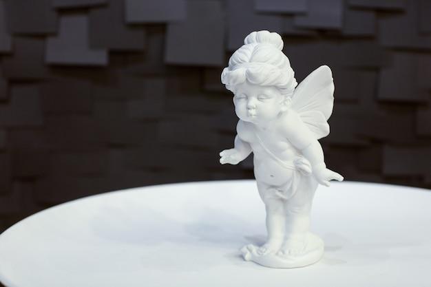 Estátua de uma menina anjo com asas em um prato branco sobre um fundo escuro