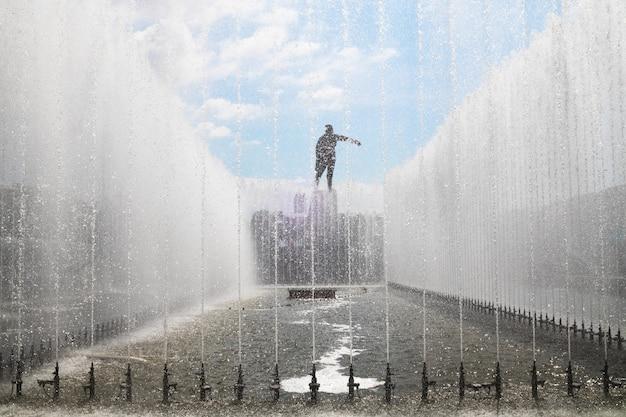 Estátua de vladimir lenin na praça de moscou através dos jatos da fonte - são petersburgo, rússia, junho de 2021.