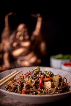 Estátua desfocada com tigela de macarrão com legumes
