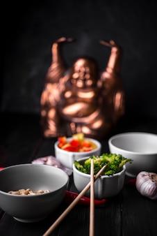 Estátua desfocada com xícaras de legumes e pauzinhos