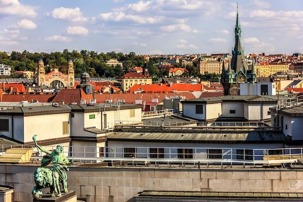 Estátua do edifício do banco nacional tcheco e a vista da torre jindrisska, praga.