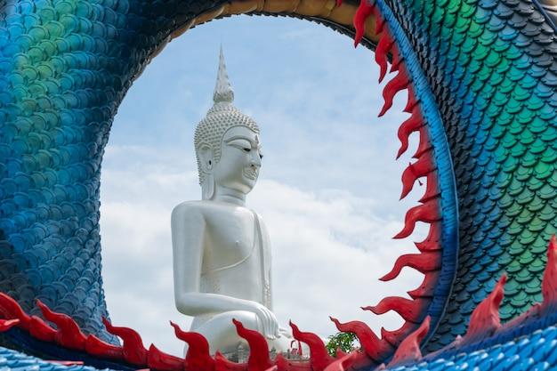 Estátua do grande buda branco no espaço do meio do ciclo das escamas de dragão