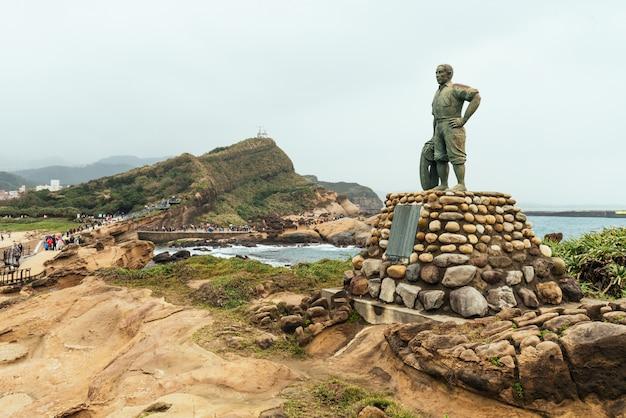 Estátua do sr. lin tien-chen no yehliu geopark, uma capa na costa norte de taiwan. uma paisagem de rochas de favo de mel e cogumelos corroídas pelo mar.