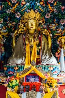 Estátua dourada de lord buddha no estilo butanês dentro do monastério butanês real em bodh gaya, bihar, índia.