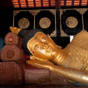 Estátua dourada do buda reclinado em wat chedi luang, chiang mai, tailândia