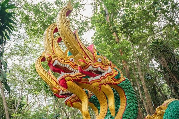 Estátua naga da ásia com fundo de floresta na zona rural da tailândia.
