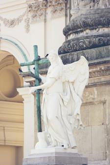 Estátua romana com uma cruz