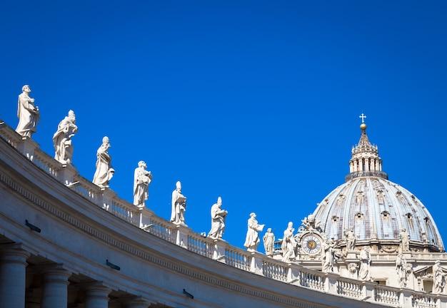 Estátuas de santos católicos. decorações na colunata bernini, catedral de são pedro, com a cúpula ao fundo - roma, itália