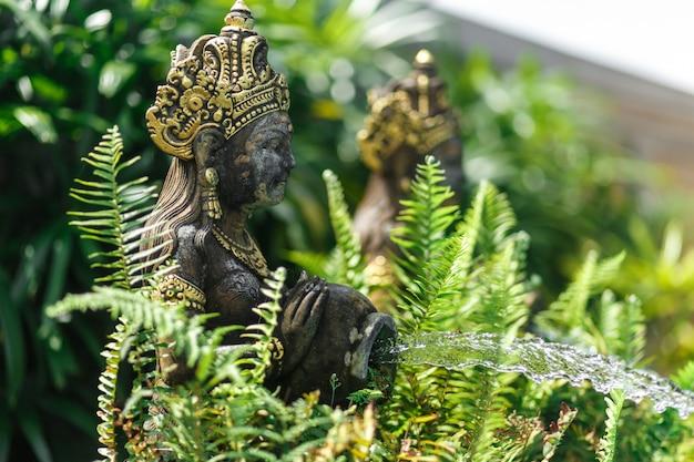 Estatueta balinesa de uma menina com uma panela da qual a água flui. decoração de piscina.