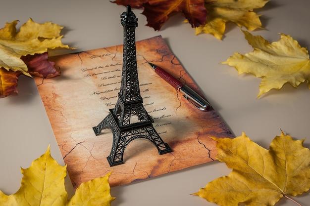 Estatueta da torre eiffel, folhas amarelas, o verso em francês, uma velha carta