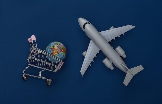 Estatueta de avião e carrinho de compras com globo sobre fundo azul clássico. entrega. cor 2020. vista superior.