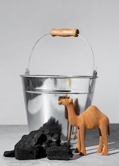 Estatueta de camelo do dia da epifania com carvão e balde