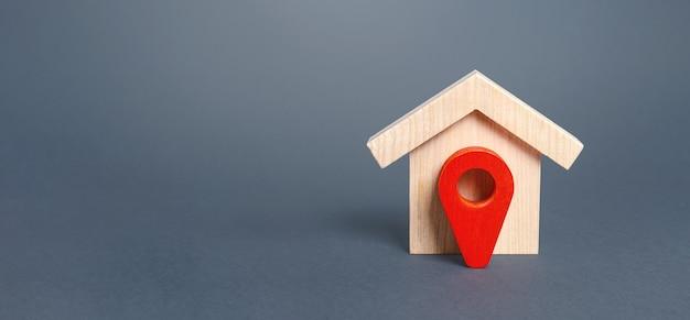 Estatueta de casa de madeira e ponteiro vermelho de localização