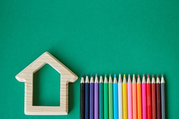 Estatueta de casa de madeira e vários lápis coloridos isolar sobre fundo verde, volta para a escola, foco seletivo