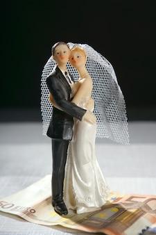 Estatueta de casal de noivos e nota de euro