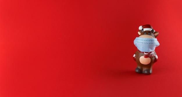 Estatueta de cerâmica de boi em máscara médica sobre um fundo vermelho com espaço de cópia. símbolo do ano novo 2021.