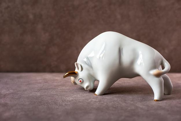 Estatueta de cerâmica de touro branco sobre fundo marrom símbolo do touro do ano