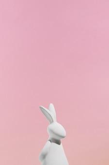 Estatueta de coelho branco em fundo rosa