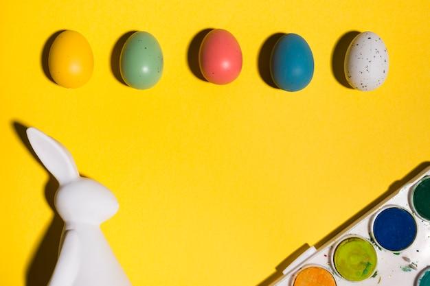 Estatueta de coelho com ovos de páscoa e tintas na mesa