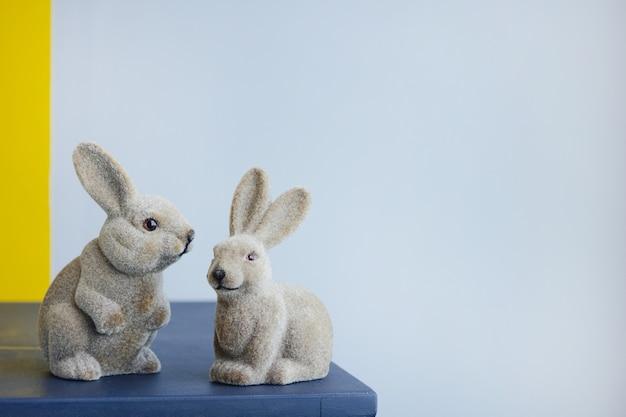 Estatueta de coelho vintage de lebres da páscoa em cerâmica em um fundo de parede cinza com copyspace