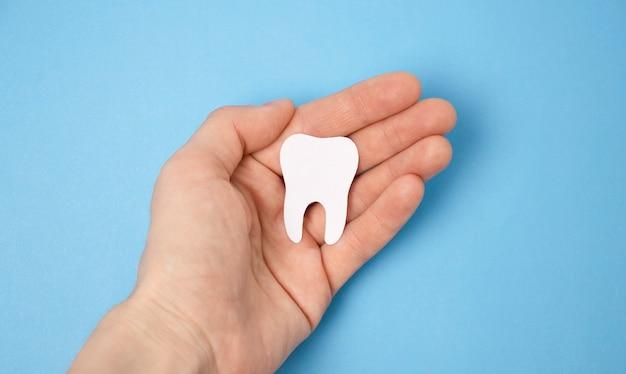 Estatueta de dente na mão sobre fundo azul. significa cuidar da cavidade oral.