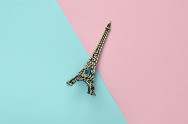 Estatueta de lembrança da torre eiffel em um fundo pastel multicolorido. tendência do minimalismo.