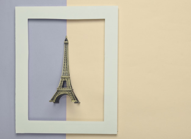 Estatueta de lembrança da torre eiffel em um quadro branco sobre um pastel colorido.