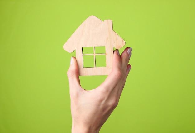 Estatueta de madeira da casa em mão feminina no verde