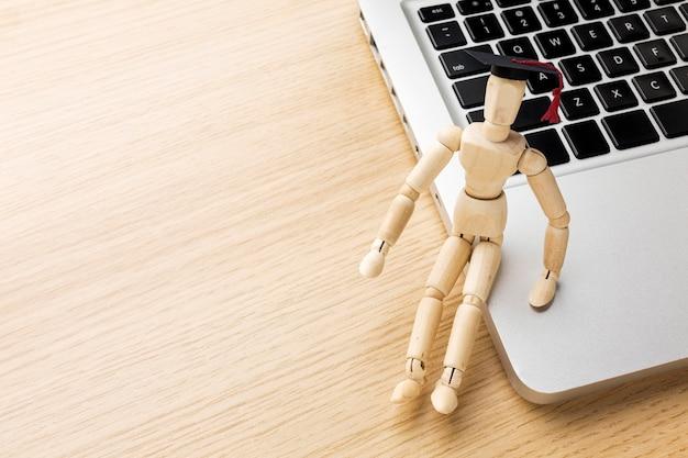 Estatueta de madeira de ângulo alto com boné acadêmico e laptop