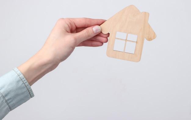 Estatueta de madeira de uma casa em uma mão feminina em um branco