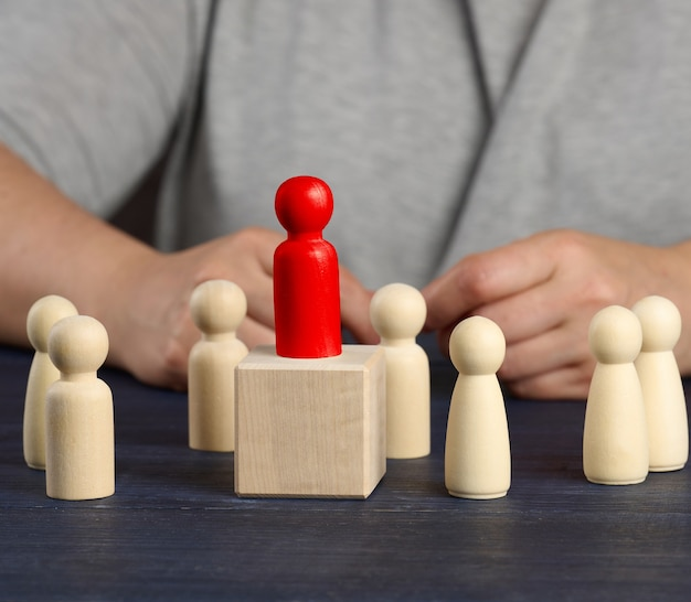 Estatueta de madeira vermelha escolhida na multidão. o conceito de encontrar funcionários talentosos, gerentes, crescimento na carreira. recrutamento de pessoal, close up