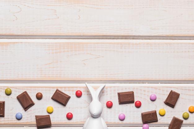 Estatueta de páscoa branca no meio de pedaços de chocolate e doces de gema em fundo de madeira