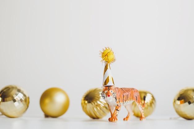 Estatueta de tigre em tampa de festa em fundo branco com bolas de natal douradas