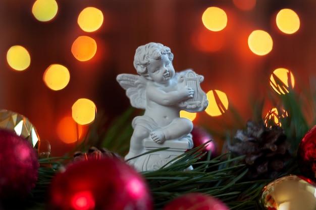Estatueta de um anjo tocando harpa em um galho de árvore de natal em um fundo de luzes de bokeh