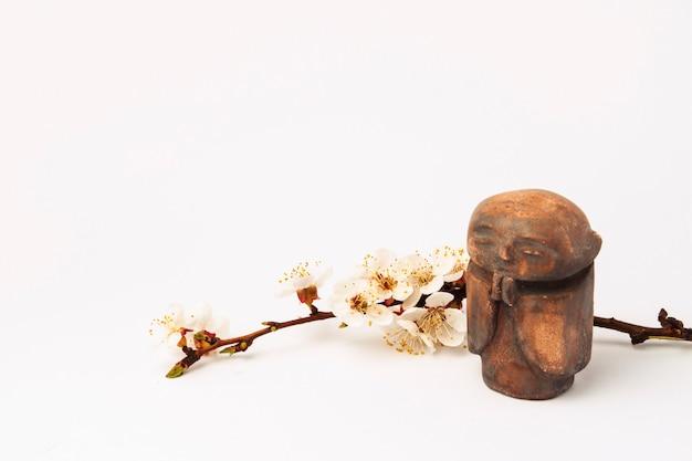 Estatueta de um monge budista e um galho de uma árvore de cereja com flores. conceito de primavera e ano novo chinês.