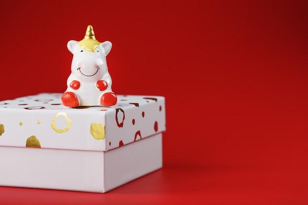 Estatueta de unicórnio em uma caixa de presente em uma parede vermelha com espaço livre. símbolo de boa sorte e sucesso.