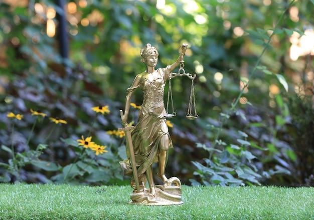 Estatueta dourada da deusa themis no gramado
