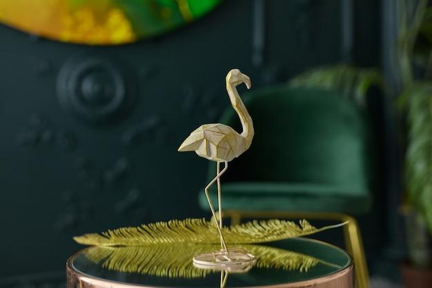 Estatueta elegante de flamingo e decoração em mesa de centro espelhada em interior art nouveau, cores dourado e verde escuro. sala de estar verde moderna - decoração da casa