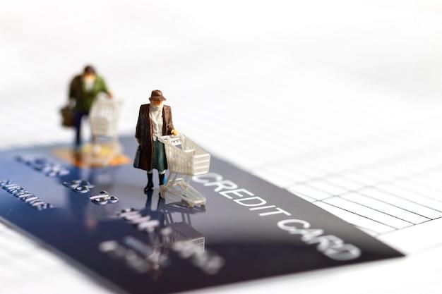 Estatueta em miniatura comprador mais velho usar máscara empurrar carrinho de compras na mock up cartão de crédito inteligente