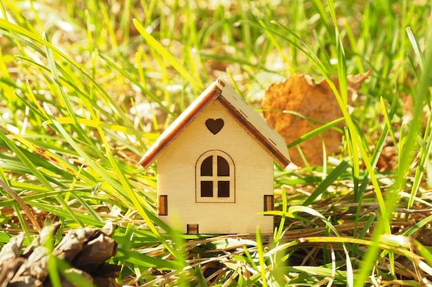 Estatueta em miniatura de uma casa de madeira na grama verde. raios solares.