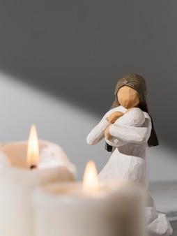 Estatueta feminina do dia da epifania com bebê e velas
