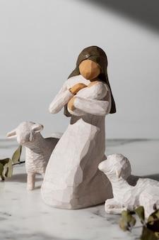 Estatueta feminina do dia da epifania com recém-nascido e ovelha