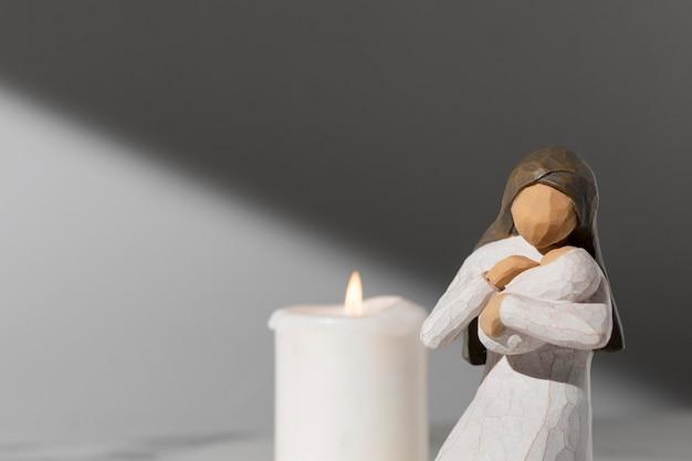 Estatueta feminina do dia da epifania com recém-nascido e vela