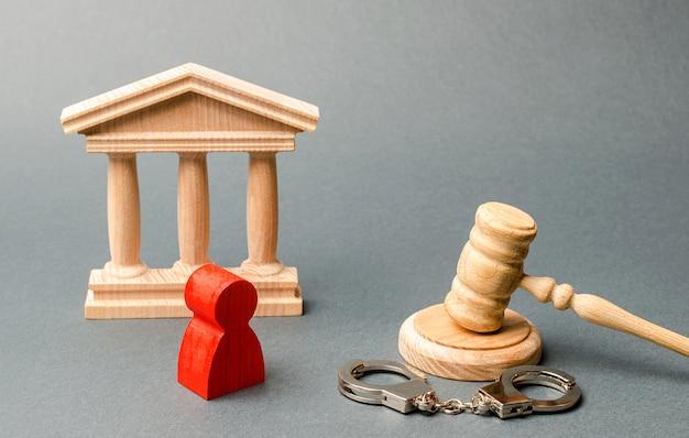 Estatueta vermelha de um homem no julgamento. proteção do réu no processo criminal.
