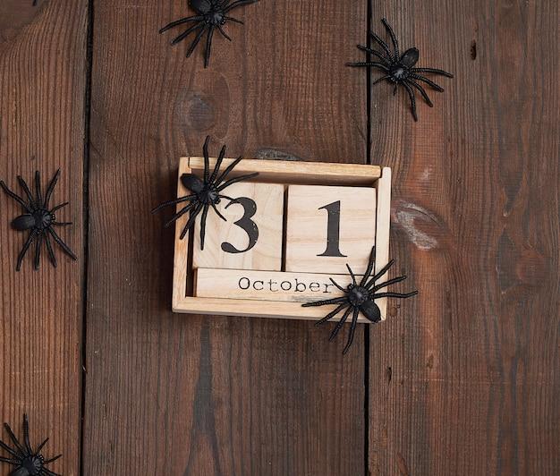 Estatuetas de aranha negra e relógio retrô de madeira feito de blocos com a data de 31 de outubro