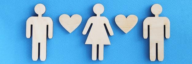 Estatuetas de madeira de homens e mulheres com corações em fundo azul