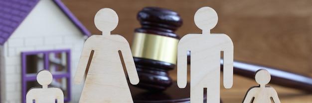Estatuetas de madeira de pais e filhos estão em cima da mesa perto da casa de brinquedos e o martelo do juiz